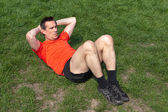 Man exercising doing Situps on the Grass in the sunshine — Stock Photo