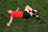 Man exercising resting and stretching on grass in the sunshine — Stock Photo
