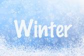 Vintern text på blå glittrig himmel och snö bakgrund — Stockfoto
