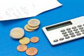 Verschiedene euro-münzen, bill und rechner auf blauem hintergrund — Stockfoto