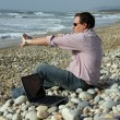 Man with laptop on beach — Stockfoto