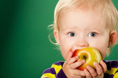 Child with an apple on a green background — Stock Photo