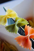 Uncooked rainbow farfalle — Stock Photo