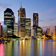 Brisbane city reflected in the river at sunset - Stock Photo