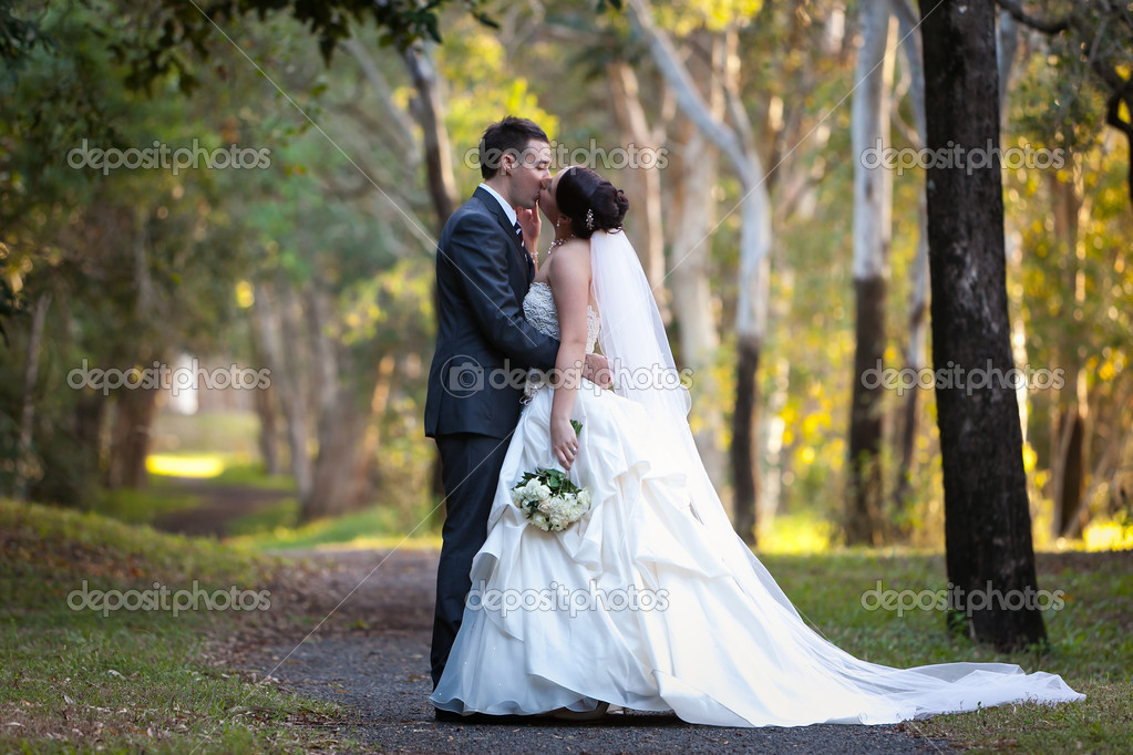 Bride and Groom kissing under trees with beautiful afternoon sunlight in the background — Stock Photo #8830250