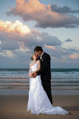 Bride and Groom hugging on the beach at sunset — Stock Photo