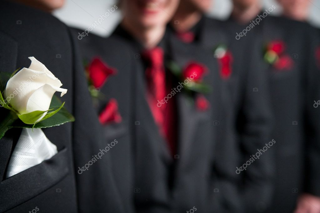 Grooms white corsage in foreground and the groomsmen with their red corsages in a row behind — Stock Photo #8863450