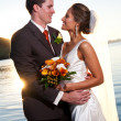 Groom holding bride at sunset with sunburst — Stock Photo