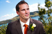 Groom and corsage with blue water in the background — Stock Photo