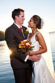 Novio novia tenencia al atardecer con sunburst — Foto de Stock