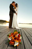Wedding bouquet in foreground and newlyweds behind — Stock Photo