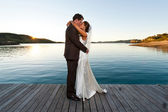 Newlyweds kissing on a jetty at sunset — Stock Photo