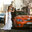 Newlyweds embracing in an alley with wedding cars - Stock Photo