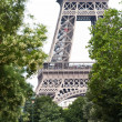 Eiffel tower glimpsed through green trees — Stock Photo