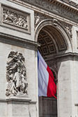 Arc de Triomphe detail showing french flag — Stock Photo
