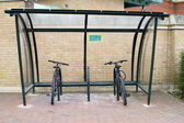 Two bikes locked to a covered bike rack — Stock Photo