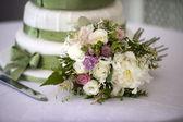 Wedding bouquet and cake — Stock Photo