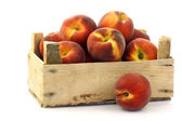Freshly harvested peaches in a wooden crate — Stock Photo