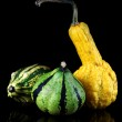 A yellow and a green striped ornamental pumpkin — Stock Photo