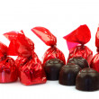 A row of bonbons wrapped in red shiny paper — Stock Photo