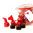 A glass jar full of delicious bonbons wrapped in shiny red paper — Stock Photo #9133340