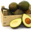 Fresh and ripe avocado's and a cut one in a wooden crate — Stock Photo #9133673