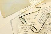 Ein paar alte gläser auf einige alte briefe — Stockfoto