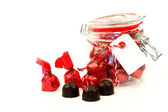 A glass jar full of delicious bonbons wrapped in shiny red paper — Stock Photo