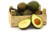 Fresh and ripe avocado's and a cut one in a wooden crate — Stock Photo