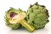 One whole and cut artichoke — Stock Photo