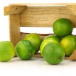 Fresh lime fruit in a wooden crate — Stock Photo