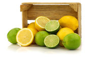 Fresh lemons and lime fruits and some cut ones in a wooden box — Stock Photo