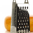 Modern metal cheese grater and a whole dutch edam cheese — Stock Photo