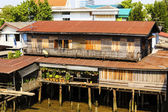Old wooden houses beside the Chao Phraya River. Bangkok, Thailan — Stock Photo
