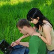 Young couple with laptop outdoor — Stock Photo