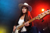 Young beautiful woman playing the guitar on the scene — Стоковое фото