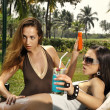 Stock Photo: Two girls on beach put sunblock cream