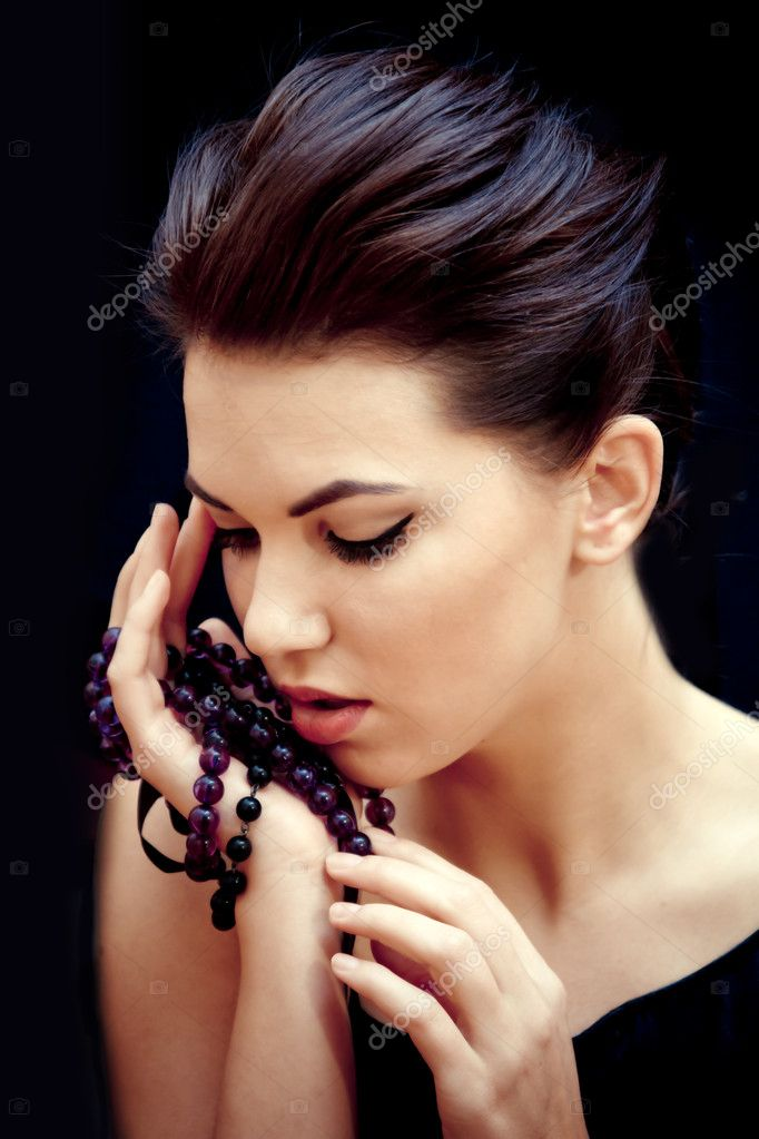 Young lady with purple beds in her hands on the black background — Stock Photo #8959220