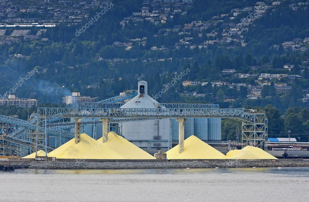 Yellow piles against blue silos in front of the mountains. — Stock Photo #8999653