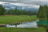 Golf course near lake near Jasper in the Canadian Rockies agains — Stock Photo