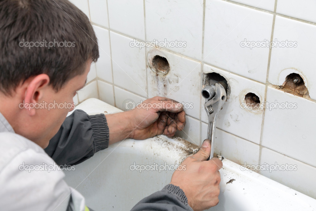 Plumber fixing pipeline with tool in hands  Stock Photo #8899585