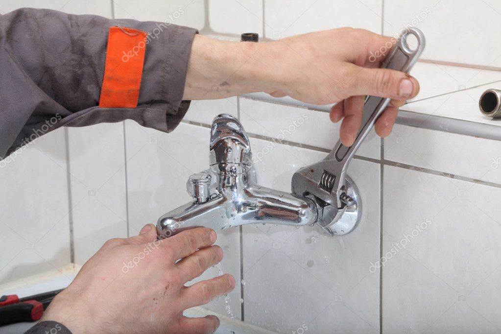 Plumber hands fixing water  tap with spanner  Stock Photo #8917799