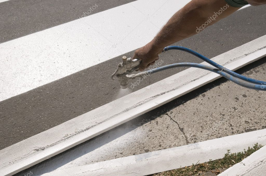 Hand spraying of pedestrian crosswalk at a street — Stock Photo #9021155