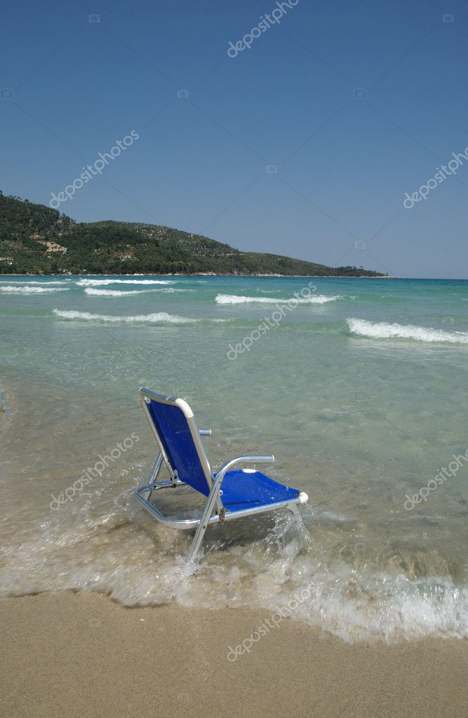 Aluminum chair in water on a beach — Stock Photo #9127257