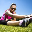 Young woman on the freshly cut grass stretching — Stock Photo