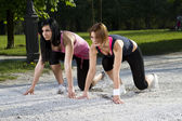 Young girls in sprinting position — Stock Photo