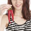Young woman holding two red chili peppers — Stock Photo