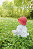 Baby girl sitting in meadow — Stock Photo