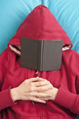 Lying down with book covering face — Stock Photo