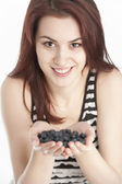 Young woman holding blueberries in her hands — Stock Photo